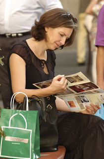 A woman reading a brochure with shopping by her side