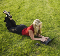 A woman lying on a lawn using her notebook computer